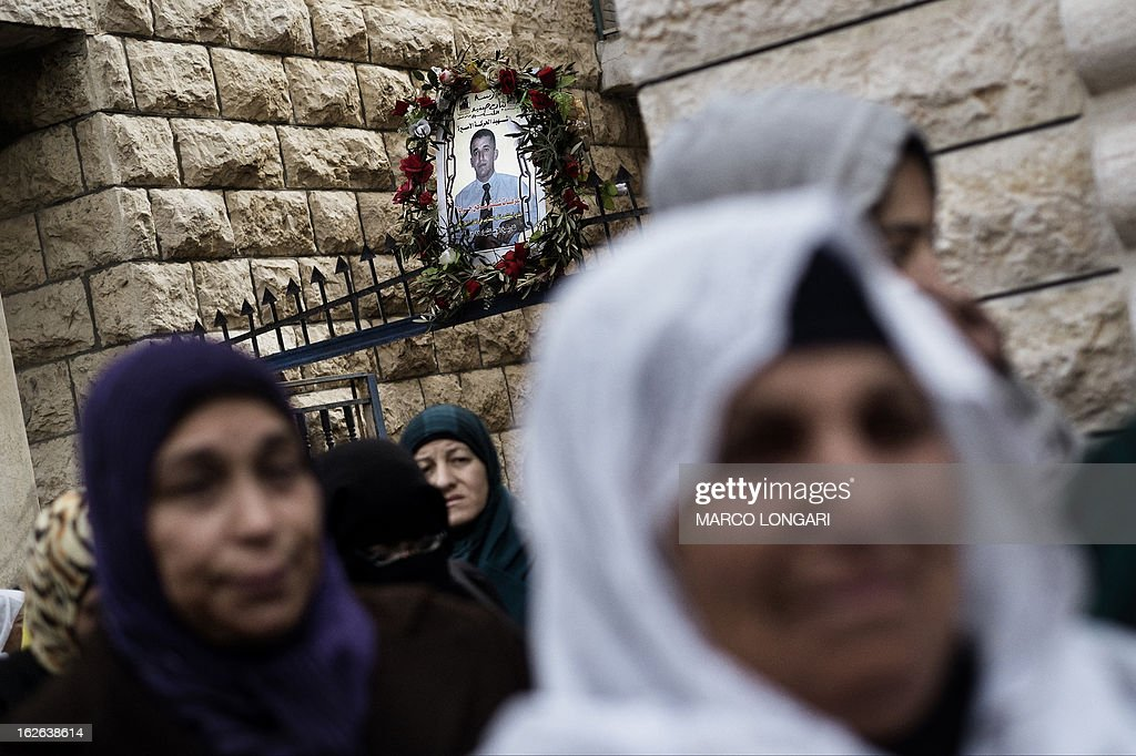 Palestinian relatives of Arafat Jaradat, who died in an Israeli prison, walk past his picture during his funeral in the West Bank village of Saair on February 25, 2013. Militants of the Al-Aqsa Martyrs Brigades, the armed wing of Palestinian president Mahmud Abbas' Fatah movement, vowed to avenge the death of Jaradat, a prisoner they say was tortured in an Israeli jail.
