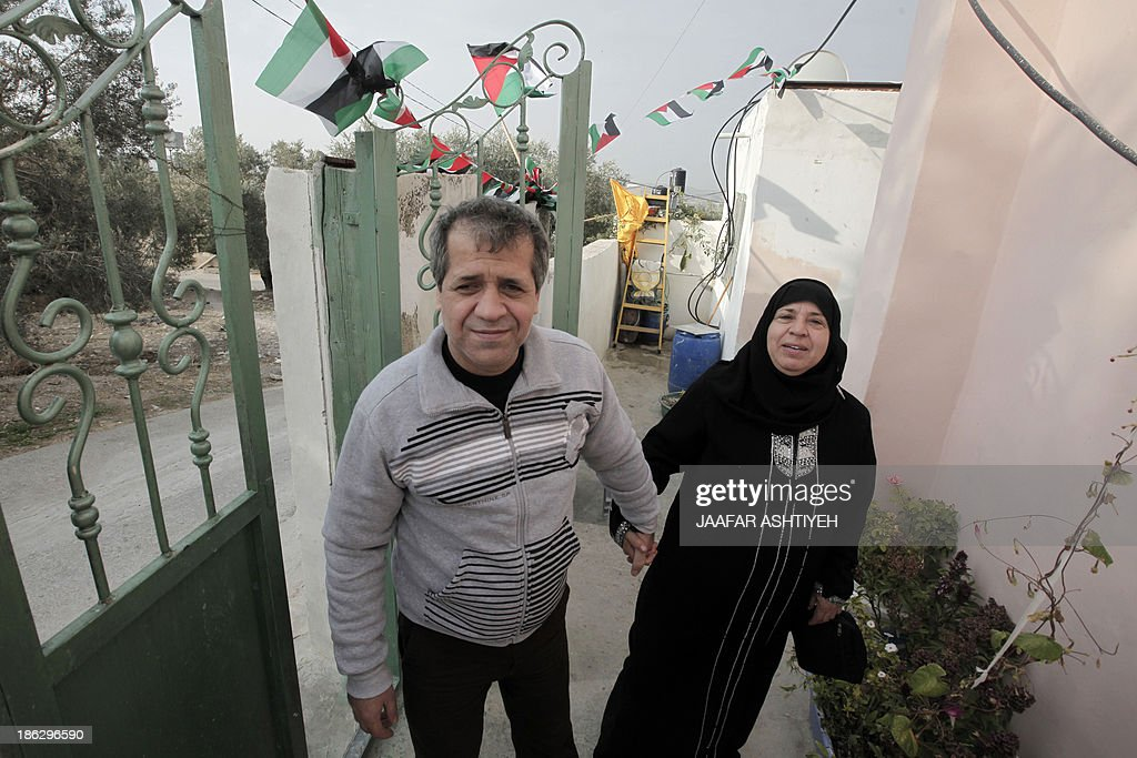 Palestinian released prisoner, Muaed Hajji poses with his mother on October 30, 2013 in the West Bank village of Burqa, west of Nablus. Israel freed 26 veteran Palestinian prisoners overnight in line with commitments to the US-backed peace process, but moved in tandem to ramp up settlement in annexed east Jerusalem.