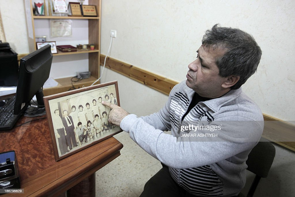 Palestinian released prisoner, Muaed Hajji shows a picture of him when he was a student on October 30, 2013 in the West Bank village of Burqa, west of Nablus. Israel freed 26 veteran Palestinian prisoners overnight in line with commitments to the US-backed peace process, but moved in tandem to ramp up settlement in annexed east Jerusalem. AFP PHOTO/JAAFAR ISHTAYEH