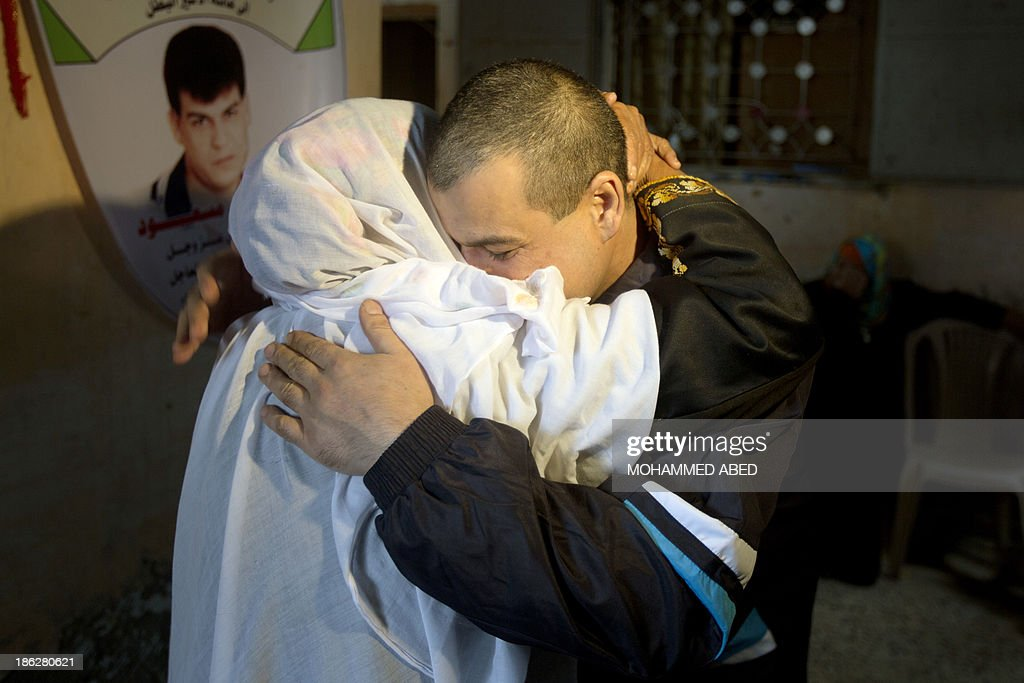 Palestinian released prisoner Omar Massud, hugs his mother at his family house in al-Shatee refugee camp in Caza City on October 30, 2013. Israel freed 26 veteran Palestinian prisoners overnight in line with commitments to the US-backed peace process, but moved in tandem to ramp up settlement in annexed east Jerusalem. AFP PHOTO/MOHAMMED ABED