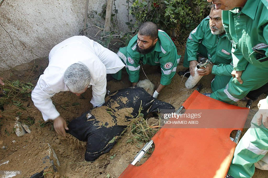 Palestinian rescue teams help a man partially buried in the sand in the garden of his house following an Israeli air strike on Beit Lahia in the northern Gaza Strip on November 15, 2012. Israeli air strikes have killed more than ten Gazans, including top Hamas commander Ahmed Jaabari, as three Israelis die when a rocket strikes a house, in the latest flareup of tit-for-tat fighting. AFP PHOTO / MOHAMMED ABED