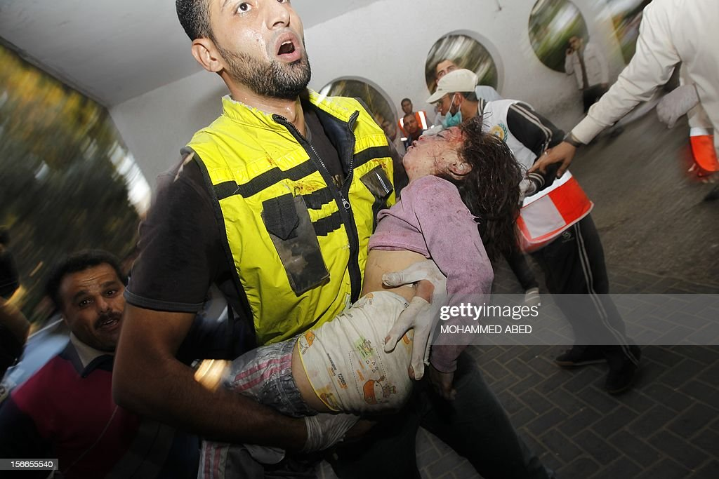 A Palestinian rescue worker carries the body of a child from the al-Dallu family into the hospital in Gaza City on November 18, 2012, after seven members of the al-Dallu family, including four children, were among nine people killed when an Israeli missile struck a family home in Gaza City, the health ministry said.