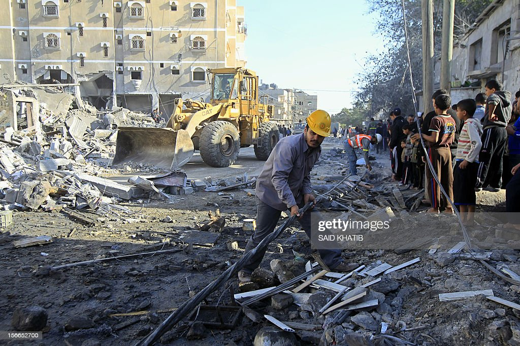 A Palestinian rescue worker inspects damaged buildings as others watch on following Israeli air strikes on the southern Gaza Strip town of Rafah on November 18, 2012. Israeli war planes hit a Gaza City media centre and homes in northern Gaza in the early morning, as the death toll mounted, despite suggestions from Egypt's President Mohamed Morsi that there could be a 'ceasefire soon.' AFP PHOTO/ SAID KHATIB