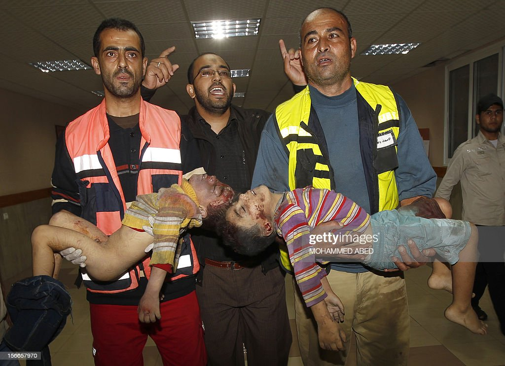 CONTENT== Palestinian rescue workers carry the bodies of two dead children from the al-Dallu family into the hospital in Gaza City on November 18, 2012, after seven members of the same family, including four children, were among nine people killed when an Israeli missile struck a family home in Gaza City, the health ministry said.