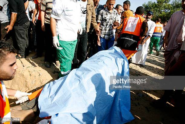 Palestinian rescue workers dig out the body of a man from the rubble of his home following an Israeli military strike on Rafah in the southern Gaza...