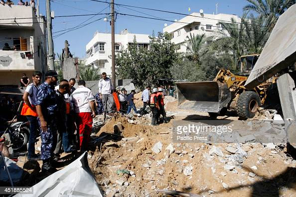 Palestinian rescue workers use a bulldozer to remove debris following an Israeli air strike in the town of Khan Yunis in the Gaza Strip Israeli...