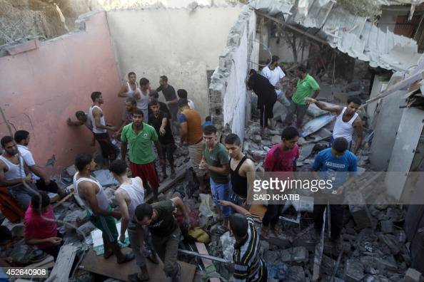 Palestinian rescuers search for victims under the rubble of the home of the Hasnen family which was destroyed following an Israeli air strike on...