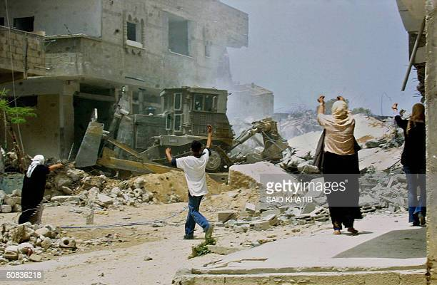 Palestinian residents of Rafah wave their hands trying to stop an Israeli army bulldozer from demolishing houses 14 May 2004 The Israeli army...