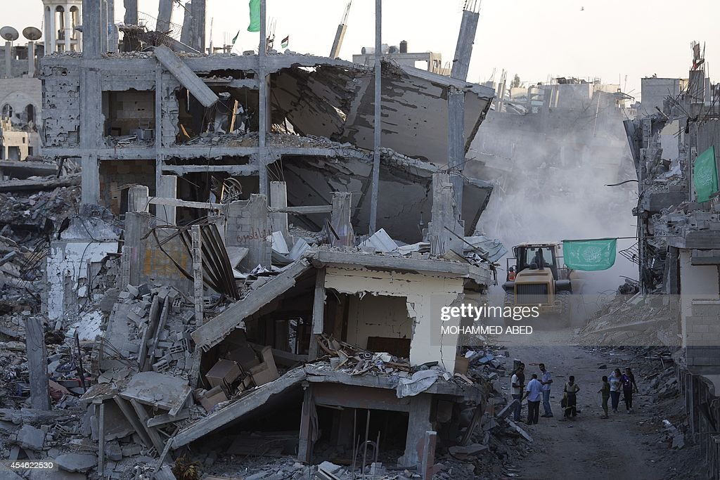 Palestinian residents stand next to their destroyed houses as a bulldozer cleans up the rubble in the Shejaiya neighbourhood of Gaza City on...