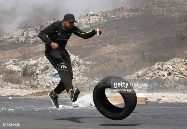 Palestinian responses Israeli security forces' tear gas attack by throwing stones and burning tyres during a demonstration to protest Israeli...