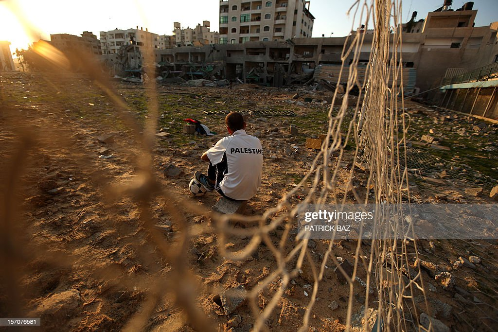 Palestinian runner and football player Bilal Abu Samaan, 20, sits in the rubble of the bombed Palestine Stadium in Gaza City on November 28, 2012. The stadium was bombed by the Israeli airforce during a conflict between the ruling Hamas party and the Israeli military between 14 and 21 November 2012.