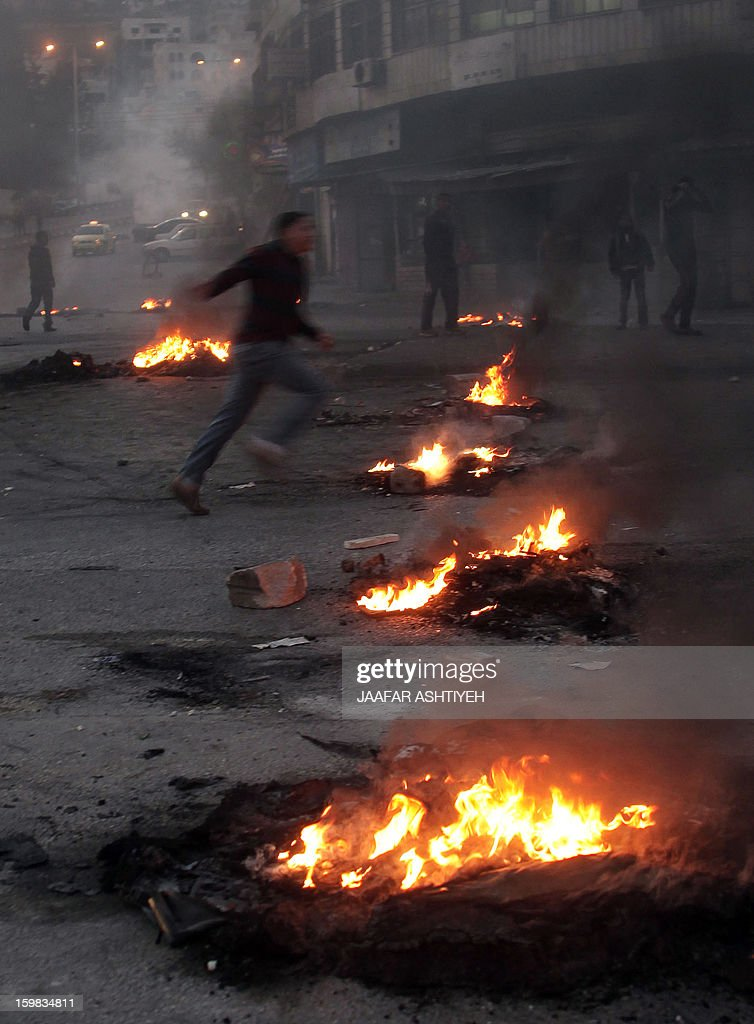 A Palestinian runs past burning tires at the entrance to the Balata refugee camp, close to the northern West Bank city of Nablus, on January 21, 2013, as he and others protesters call for the release of several gunmen arrested two days ago by Palestinian security.