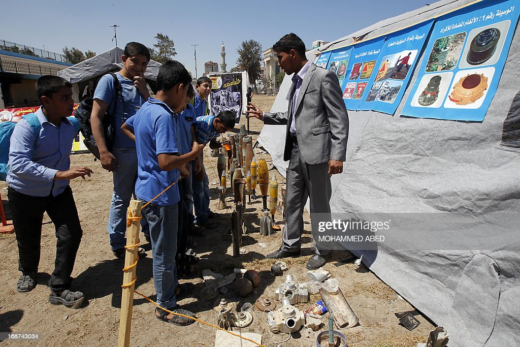 Palestinian school boys look at the remains of Israeli explosive devices which were used against the Gaza Strip during an exhibition in Gaza City, on May 14, 2013. Palestinians are preparing to mark Nakba Day on May 15 which commemorates the exodus of hundreds of thousands of their kin after the establishment of Israel state in 1948.