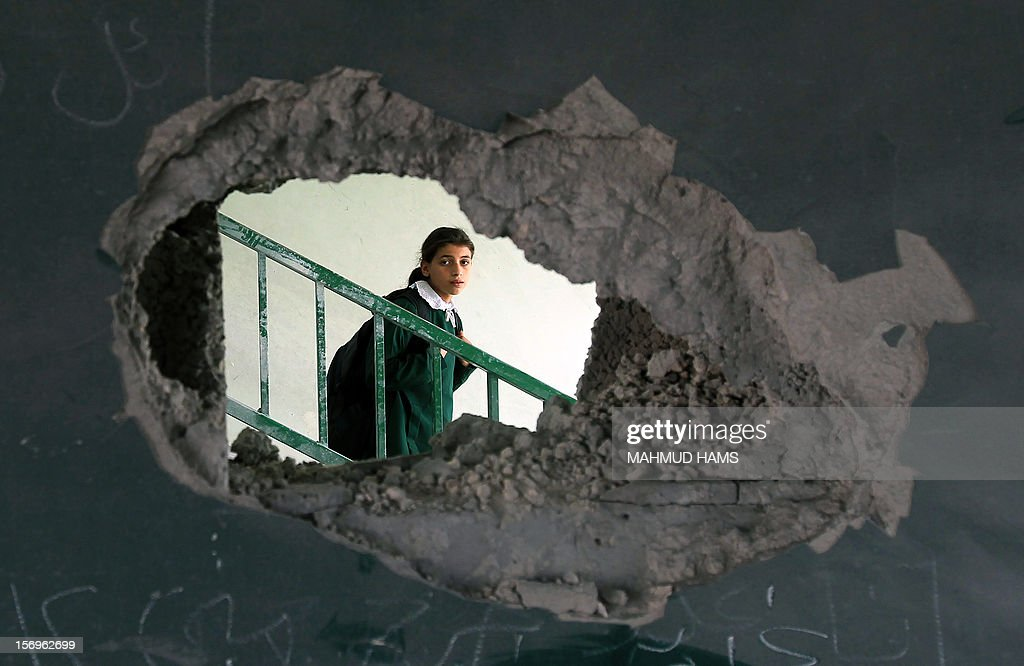 A Palestinian school girl appears through a hole in a wall in a Gaza city damaged school on November 26, 2012.