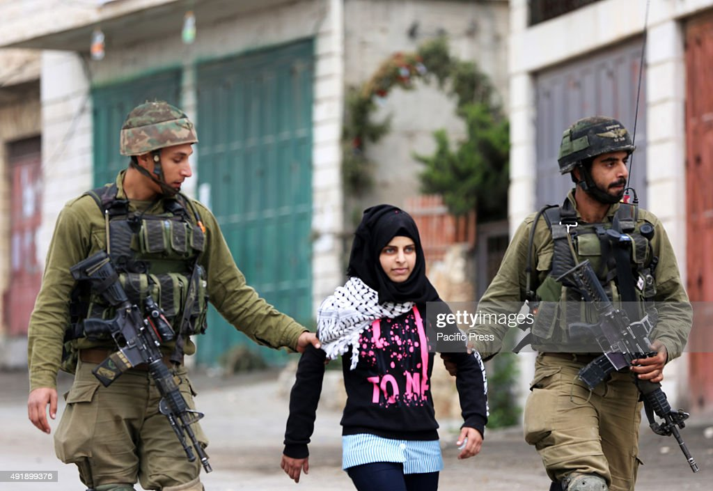 Palestinian school girl is arrested and taken away by Israeli soldiers during clashes with Palestinian demonstrators in the West Bank town of Beit...