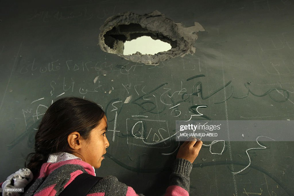A Palestinian school girl writes on the blackboard of a classroom, damaged during last week's Israeli offensive, at a school in Gaza City, on November 24, 2012, three days after a truce was declared between Israel and Hamas. Gaza's children, virtually absent from the streets since the violence, are beginning to return to school after a truce between Israel and Gaza's Hamas rulers ended eight days of deadly bombardment. AFP PHOTO/MOHAMMED ABED