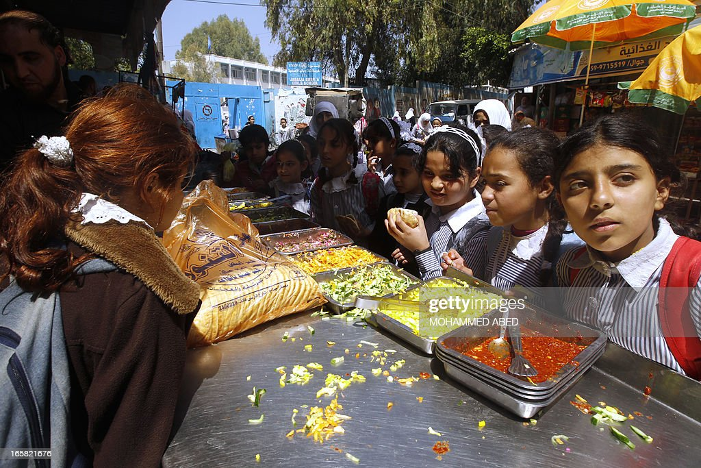 Palestinian school girls gather to buy falafel in the Jabalia refugee camp in the northern Gaza Strip on April 6, 2013. Gaza's Hamas rulers urged the United Nations to reconsider its suspension of food aid for Palestinian refugees, imposed after protesters stormed a UN depot.