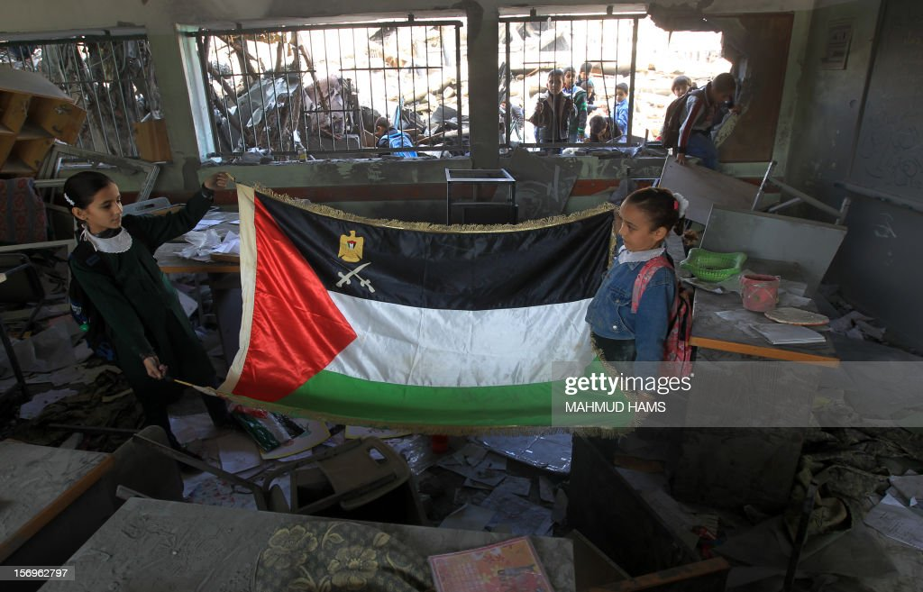 Palestinian school girls hold a Palestinian flag with their school, in a damaged class room on November 26, 2012 in Gaza city. The school was damaged some days ago, before a truce between Hamas and Israel ended eight days of cross border attacks in which 166 Palestinians and six Israelis died.