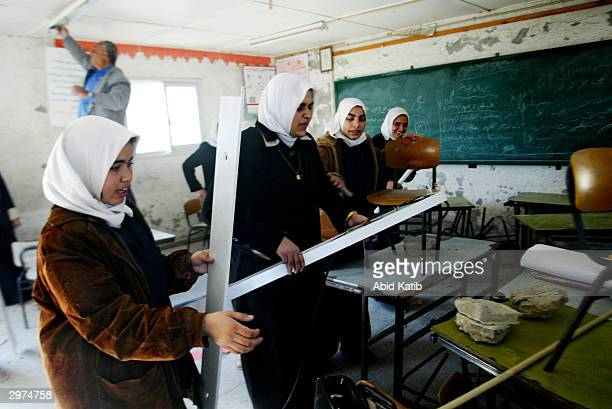 Palestinian school girls inspect their damaged classroom in the Rabaa AlAdaweia high school that was destroyed by Israeli forces February 12 2004 in...