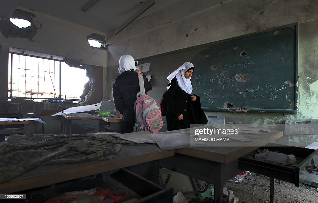 Palestinian school girls walk in a destroyed class room on November 26, 2012 in Gaza city. The school was damaged some days ago, before a truce between Hamas and Israel ended eight days of cross border attacks in which 166 Palestinians and six Israelis died.