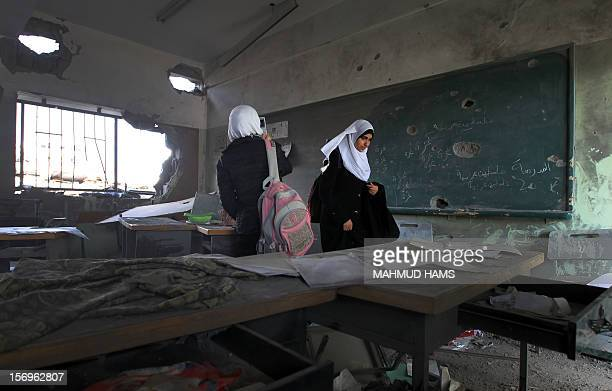 Palestinian school girls walk in a destroyed class room on November 26 2012 in Gaza city The school was damaged some days ago before a truce between...