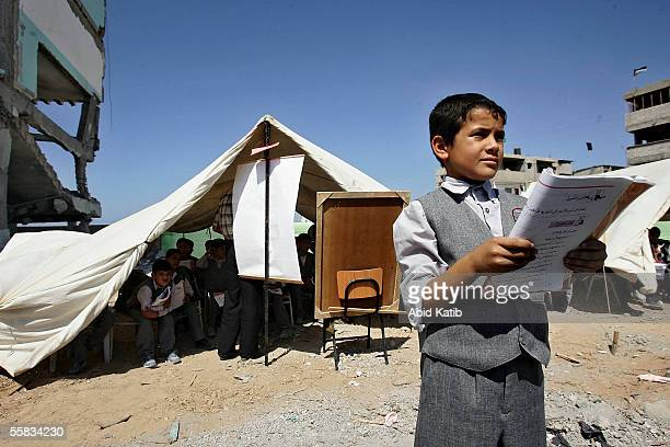 Palestinian schoolboy stands near a makeshift tent classroom as he and other students study outside their destroyed classroom at Dar AlArqam...