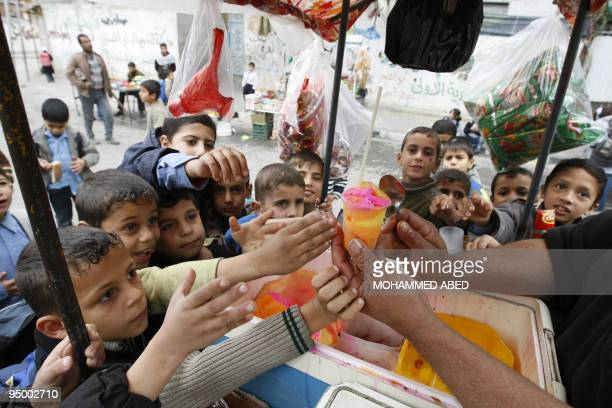 Palestinian schoolboys take ice cream from a street vendor outside their school in Beit Lahia in the northern Gaza Strip on December 16 2009 Israel...