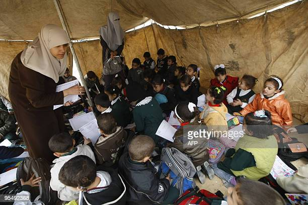 Palestinian schoolchildren attend a lesson under a tent at the yard of their Islamic school which was destroyed during Israel's threeweek military...