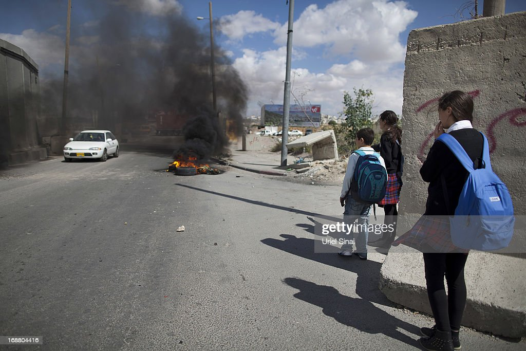 Palestinian schoolchildren walk home from school as tires burn during clashes between Palestinian protesters and the Israeli army during Nakba day on May 15, 2013 near the Qalandia checkpoint at the outskirts of Ramallah, the West Bank. Palestinians mark Israel's establishment in 1948 with 'Nakba' or 'catastrophe' day on May 15, to remember the thousands of Palestinians who fled or were expelled during the creation of the Jewish state and the subsequent war.