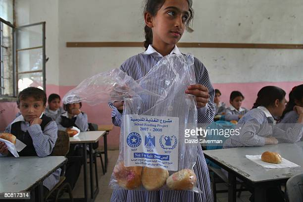 Palestinian schoolgirl distributes vitaminenriched snacks provided daily by the World Food Program to her classmates April 21 2008 in the West Bank...