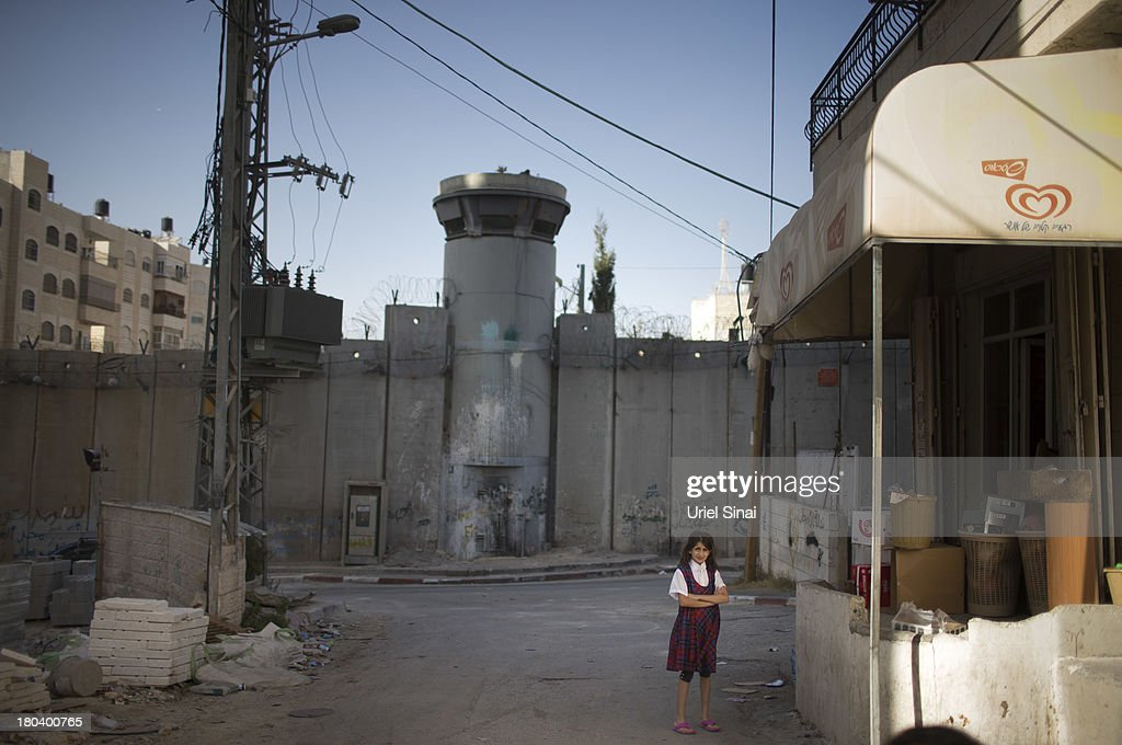 A Palestinian schoolgirl stands near the Israeli West Bank barrier on the outskirts of Jerusalem on September 12, 2013 in Aram, West Bank. The twenty-year anniversary of the Oslo Accord, which was to set up a framework for peace between Israel and Palestine, will be marked on September 13.