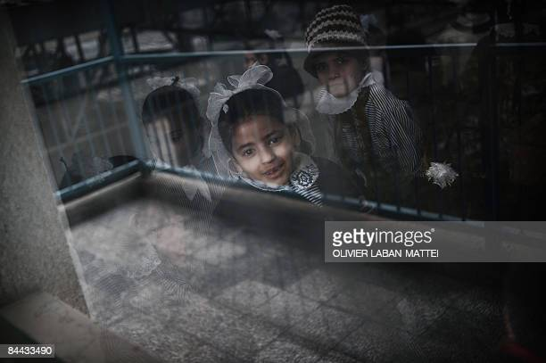 Palestinian schoolgirls smile behind the window of their classroom at UNRWA's primary school in Beit Lahia in the northern Gaza Strip on January 24...