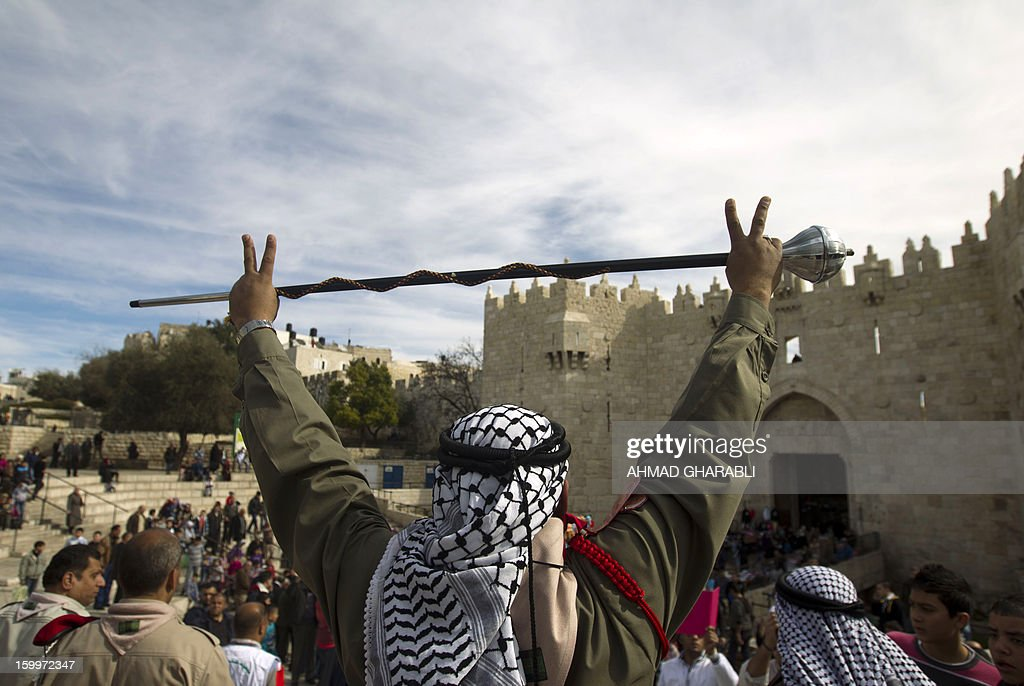 A Palestinian scout waves a baton as a sign of victory during a ceremony commemorating the birth of Prophet Mohammed, known in Arabic as 'al-Mawlid al-Nabawi' at the entrance of Jerusalem's Old City next to the Damascus Gate on January 24, 2013. AFP PHOTO/AHMAD GHARABLI