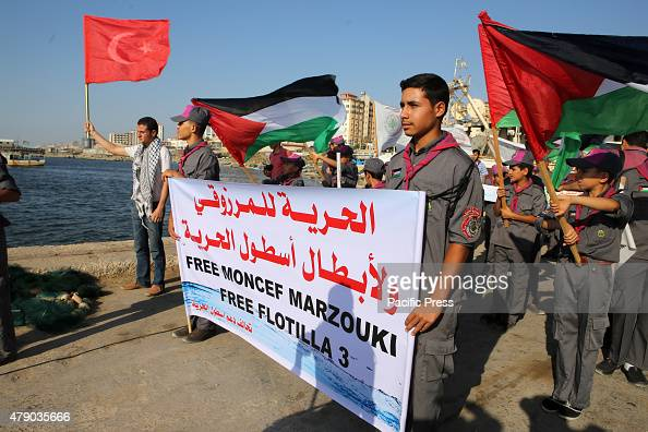 Palestinian scouts hold banners and their national flag during a protest against the Israeli blocking of a boat of foreign activists from reaching...