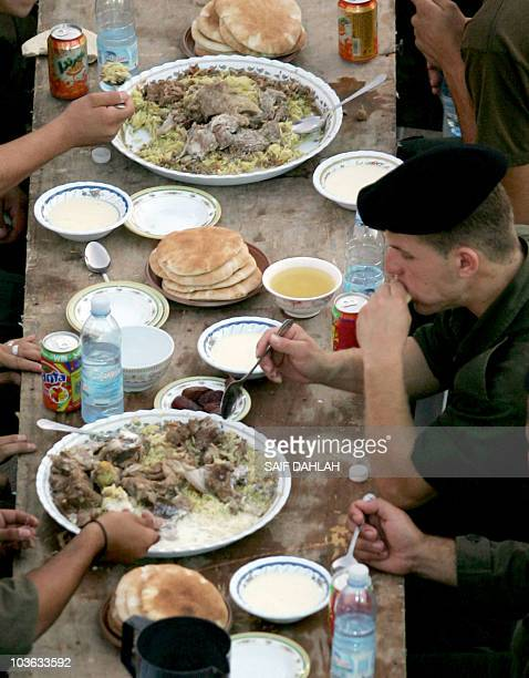 Palestinian security forces break their daylong Ramadan fast over a group 'Iftar' meal of traditional Mansaf at the police headquarters in the West...
