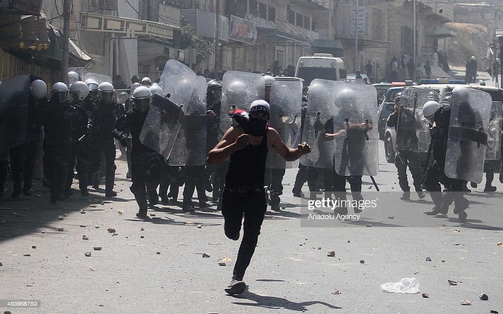 Palestinian security forces intervene protestors following a protest to show support for resistance movement Hamas in Hebron, West Bank on August 22, 2014.