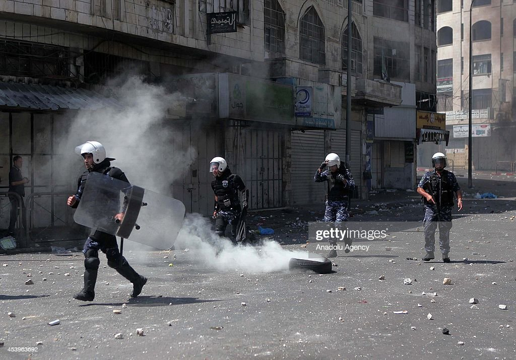 Palestinian security forces intervene to hundreds of Palestinians as they staging solidarity demonstration after Friday Prayer for Hamas in Hebron, West Bank on August 22, 2014.