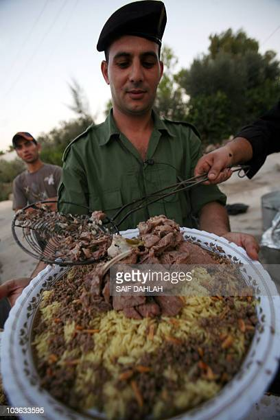 Palestinian security forces prepare to break their daylong Ramadan fast over a group 'Iftar' meal of traditional Mansaf at the police headquarters in...