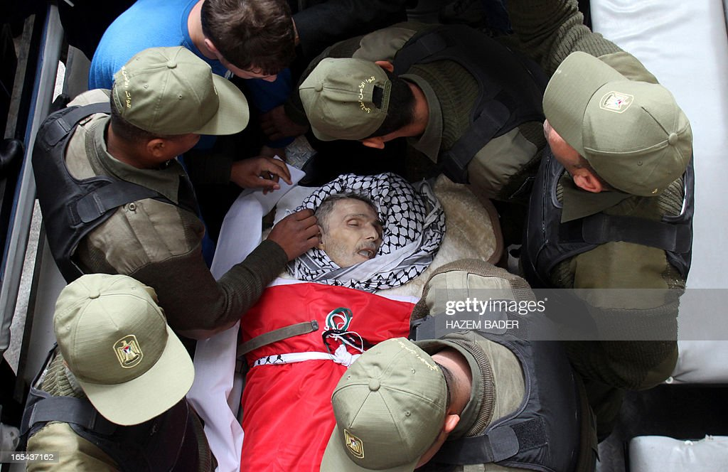 Palestinian security forces surround the body of Maisara Abu Hamdiya, a Palestinian prisoner who died of cancer while in Israeli detention, during his funeral procession in the West Bank city of Hebron April 4, 2013. The West Bank simmered with anger as thousands joined the funeral of a prisoner who died in an Israeli jail and similar numbers gathered to bury two teens shot dead overnight. AFP PHOTO/HAZEM BADER