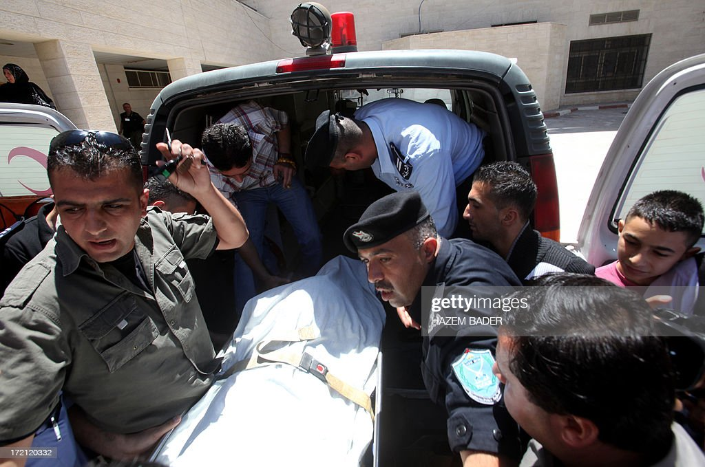 Palestinian security forces wheel the body of Palestinian youth Moataz Sharawna, 19, upon his arrival for an autopsy at a hospital in the West Bank city of Hebron on July 2, 2013 after he was knocked down and killed by an Israeli military jeep during overnight clashes in the West Bank village of Dura. Sharawna died after being hit by the vehicle after several hours of clashes between stone throwers and troops which began at midnight in Dura, which lies just southwest of Hebron, a police spokesman told AFP. AFP PHOTO/HAZEM BADER