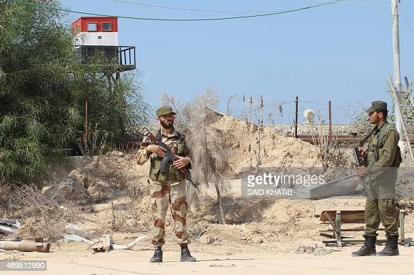 Palestinian security men stand near an Egyptian watch tower on the border between Egypt and Gaza in Rafah southern Gaza Strip on September 21 2015...