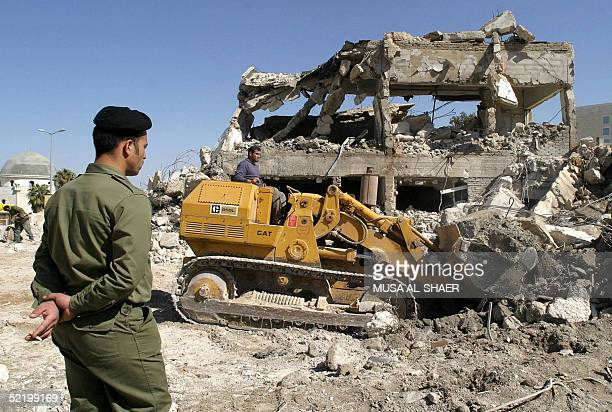 Palestinian security officer watches a Palestinian bulldozer clearing the rubble of the former offices of the Palestinian Authority in Bethlehem...