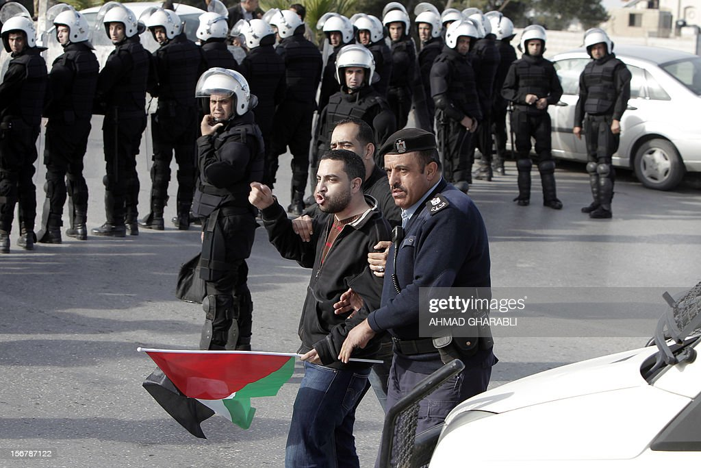 Palestinian security personnel detain a protestor during a demonstration against US Secretary of State Hillary Clinton's visit in the West Bank city of Ramallah on November 21, 2012. US Secretary of State Hillary Clinton expressed 'rock solid' support for Israel's security while calling for a de-escalation of the conflict in Gaza where fighting entered its eighth day, despite signs of an emerging truce.