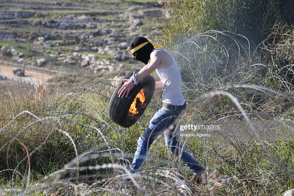 A Palestinian sets a tyre on fire during a protest against Israel's practices, its settlement policies, its decision on administrative detention and the continuing detention of journalist Mohammed al-Kayak who has been on hunger strike for 80 days against arbitrary measures, in front of Ofer prison in the west of the city of Ramallah on the West Bank on February 12, 2016. Palestinians threw back tear gas capsules used in an intervention by the Israeli security forces.
