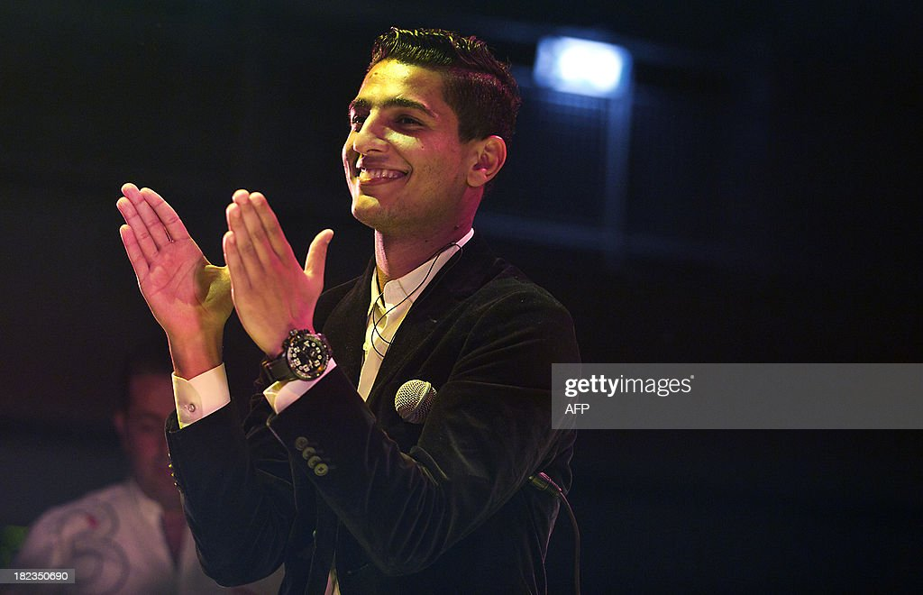 Palestinian singer Mohammed Assaf, Gazan winner of the Arab Idol talent competition, a rare symbol of Palestinian unity, applauds during his first concert outside the Arab world on September 29, 2013 in The Hague, The Netherlands. Assaf, 24, became a national hero when he won the pan-Arab contest in June after transfixing millions of television viewers with his soaring renditions of Arab love ballads and patriotic Palestinian songs. Organisers said they expected the 800 tickets for the young heartthrob's concert in The Hague's town hall on Sunday night, his first outside the Middle East and north Africa, to be sold out.