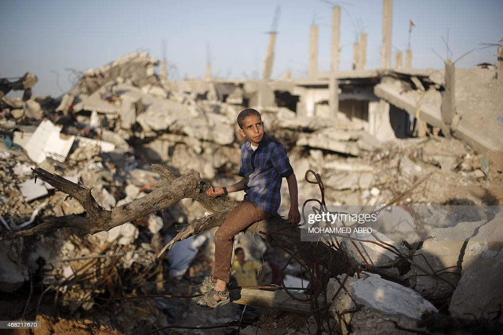 A Palestinian sits amid the rubble of buildings that were destroyed during the 50day war between Israel and Hamas militants in the summer of 2014 in...