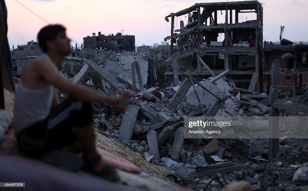 A Palestinian sits among the debris of destroyed buildings as Palestinians start to return their homes during ceasefire in al-Shaaf neighborhood Gaza City, Gaza on August 31, 2014.