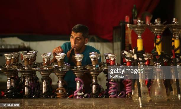 A Palestinian smokes shisha or hookah at a Royal Plaza Cofee shop in Gaza City on May 9 2017