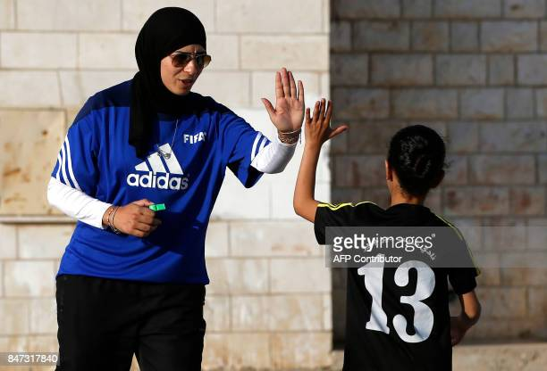Palestinian sports teacher Rajaa Hamdan leads a football training session with young girls in the northern West Bank village of Deir Jarir near...