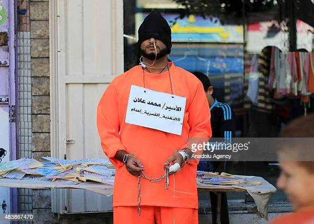 Palestinian stages a protest as he bind himself with chains demanding the release of hunger striker Palestinian lawyer Muhammad Allan who is under...